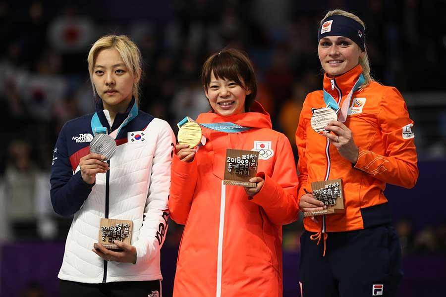 高木菜那(中央)らとともに、真剣な表情で銀メダルを掲げるキム・ボルム(右)。【写真:Getty Images】