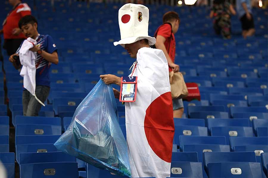 ベルギー戦後に客席のゴミを拾い集める日本のサポーター【写真:Getty Images】