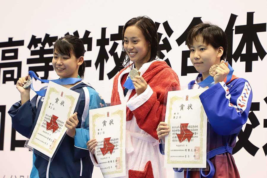 今井月(中央)は1分07秒41の大会新記録で女子100メートル平泳ぎ3連覇を飾った【写真:荒川祐史】