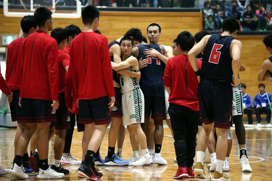 勝利後、相手選手と抱擁を交わす福岡第一の河村(中央8番)と松崎(中央右)【写真:平野貴也】