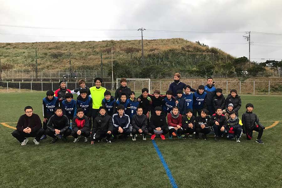 地元八丈島のサッカー少年達と記念写真を撮る選手達【写真提供:一般社団法人 JAPAN体幹バランス指導者協会】