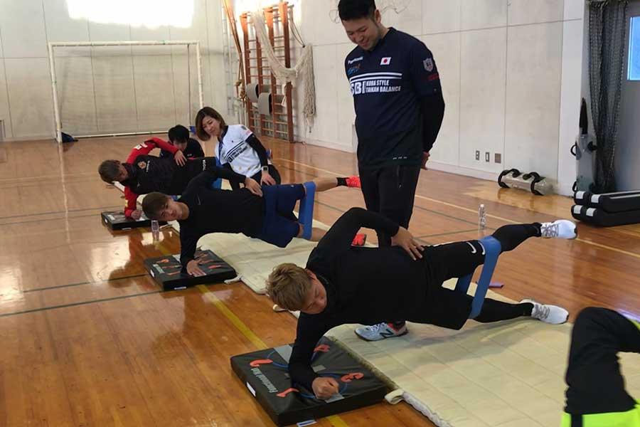 八丈島到着後、体育館で体幹トレーニングに励む鹿島FW安部(写真・手前から二番目)【写真提供:一般社団法人 JAPAN体幹バランス指導者協会】