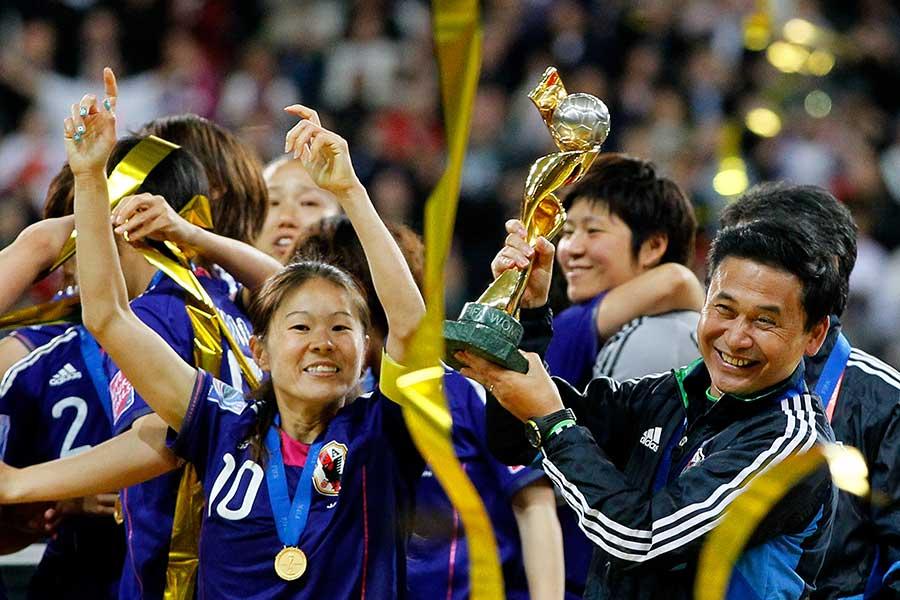 11年W杯を制し、澤穂希(左)と優勝トロフィーを掲げる佐々木則夫氏【写真:Getty Images】