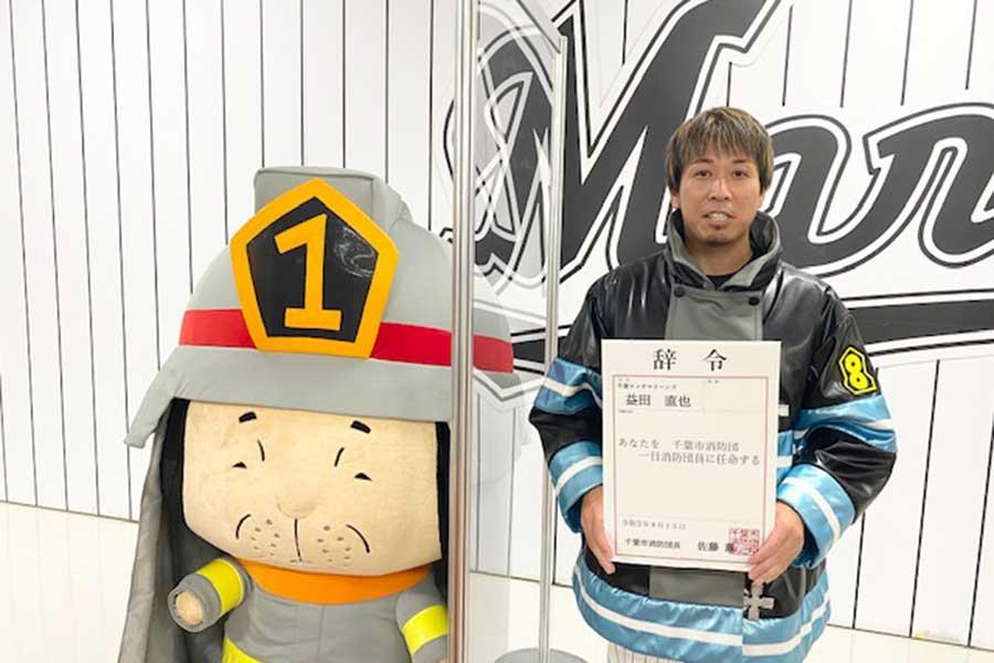 千葉消防団一日消防団員に任命された益田(右)は人気漫画「炎炎ノ消防隊」に登場するマスコットのまもる君と笑顔【写真:球団提供】