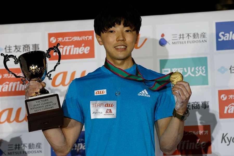 プロ転向初戦で優勝した藤井快は、記念撮影で笑顔を見せた
