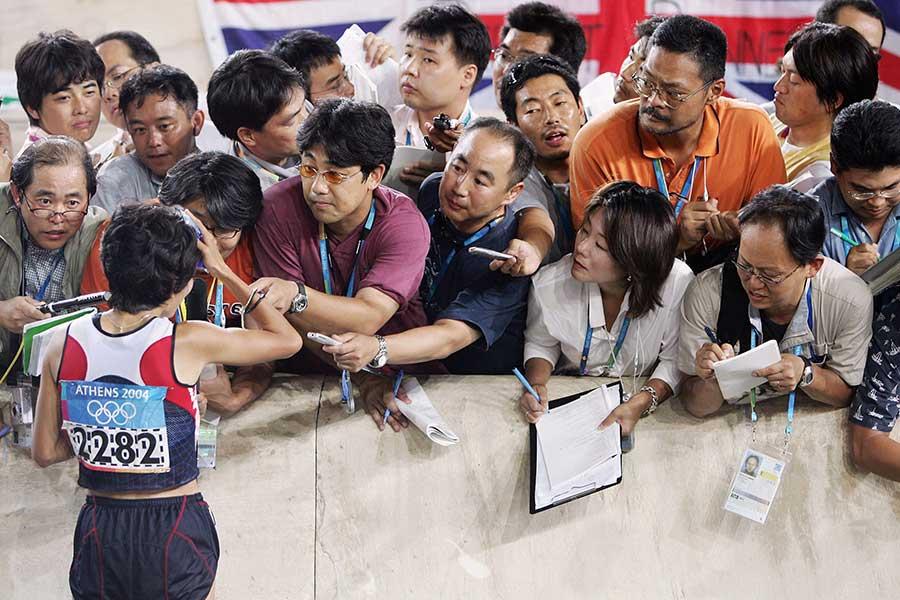 金メダル獲得後に取材を受ける野口みずきさん(左)、選手とメディアの正しい距離感とは【写真:Getty Images】