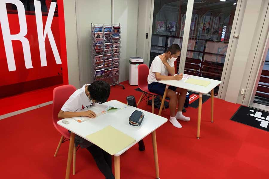 自習室でスタッフのサポートを受けながら、思い思いの課題に取り組む子どもたち【写真:編集部】