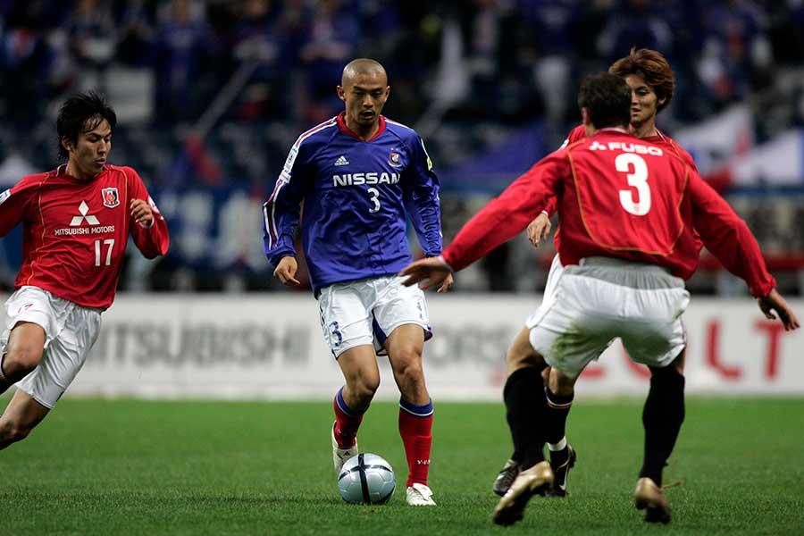 2004年、長髪をばっさりと切り坊主頭でプレーする松田直樹さん【写真:Getty Images】